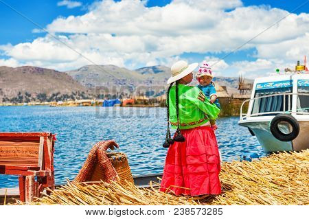 Titicaca Lake, Puno, Peru - March, 20, 2017: Woman In Traditional Dresses With Her Child On Uros Flo