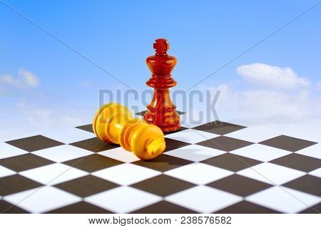 Two Chess Kings On Board, One Standing, One Lying Down, Blue Sky And White Clouds Background. Looks