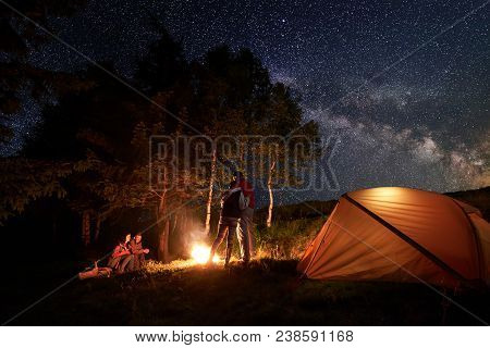Tourists During A Night In Camping Around A Campfire Near Orange Tent. One Pair Is Hugging Each Othe