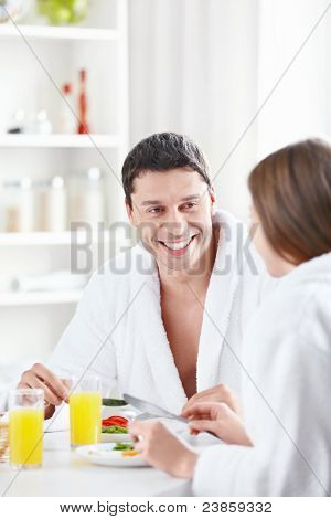 Attractive young couple eating breakfast in the kitchen