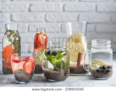 Different Chia Water In Glass On Gray Background. Chia Infused Detox Water With Berries, Fruits And