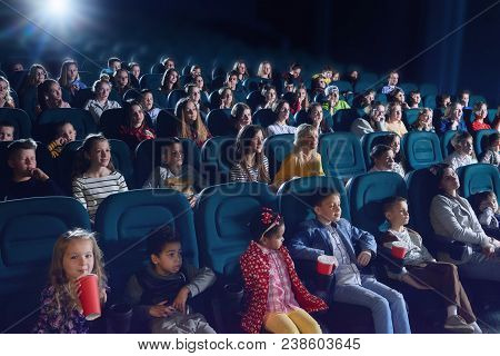 Crowd Of People Sitting In Comfortable Seats In Modern Movie Theatre. Children, Teens, Adults Watchi