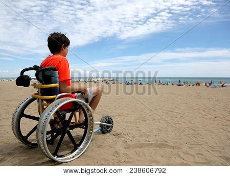 Boy On The Special Wheelchair With Aluminum Alloy Wheels On The Beach In Summer