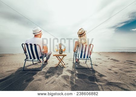 Couple On A Deck Chair Relaxing On The Beach. Happy Couple Enjoy On The Beach During Summer Vacation