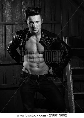 Handsome Sexy Sensual Muscular Stylish Young Man In Leather Jacket With Bare Torso Standing Indoor O
