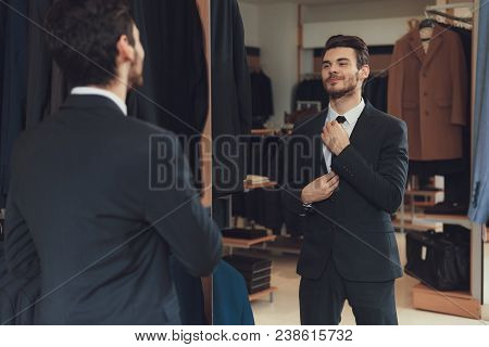 Confident Cheerful Man Ties Up Tie In Showroom Of Men Business Clothes Store. Dressing Room. New Sui