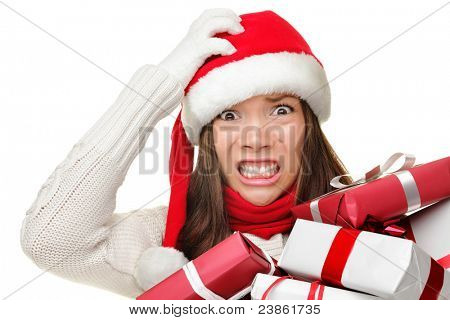 Christmas stress - busy woman wearing santa hat stressing for christmas shopping holding may christmas gifts in her arms. Funny image of Asian Caucasian female model isolated on white background.