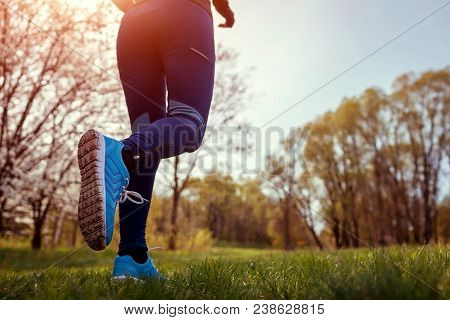 Young Woman Running In Spring Forest In The Morning. Close-up Of Sneakers. Helathy Lifestyle. Mornin