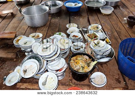 Plate, Bowl, Spoon. Have Not Washed. Are Stack On Wooden Board. Food Waste Stuck. Have A Full Tank O