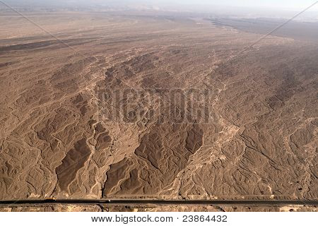 Flight over Nazca lines - Dry river bed aerial view with a road - Peru poster