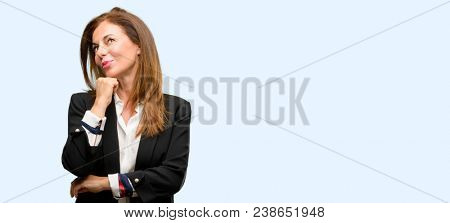 Middle age woman wearing jacket thinking and looking up expressing doubt and wonder isolated blue background