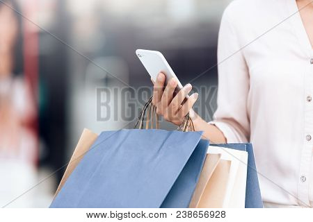 Woman With Shopping Bags And Smartphone In Shopping Center. Shopping Concept.