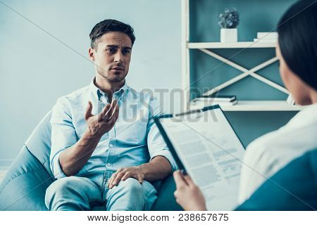 Young Upset Man At Psychologist Reception. Consulting Psychologist Reception.