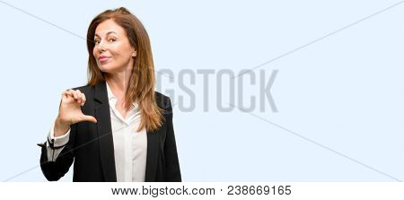 Middle age woman wearing jacket proud, excited and arrogant, pointing with victory face isolated blue background