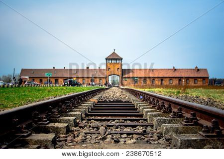Main Gate To Nazi Concentration Camp Of Auschwitz Birkenau With Train Rail, Poland On April 14, 2018