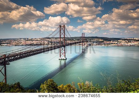 The 25 De Abril Bridge Is A Bridge Connecting The City Of Lisbon To The Municipality Of Almada On Th