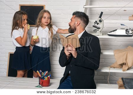 Teacher Man Read Story To Girls Eating Apple. School Time Of Sisters And Father In Library. Educatio