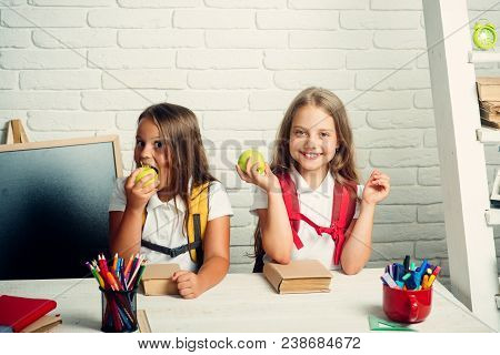 Little Girls Eat Apple At Lunch Break. Back To School And Home Schooling. Friendship Of Small Sister