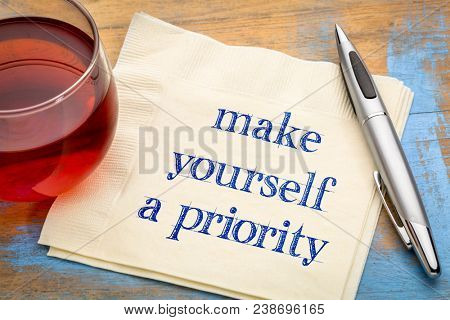 Make yourself a priority advice - handwriting on a napkin with a cup of tea