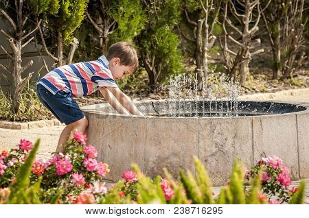 Happy Cute Caucasian Kid Playing With Water Fountain In The Public Park.