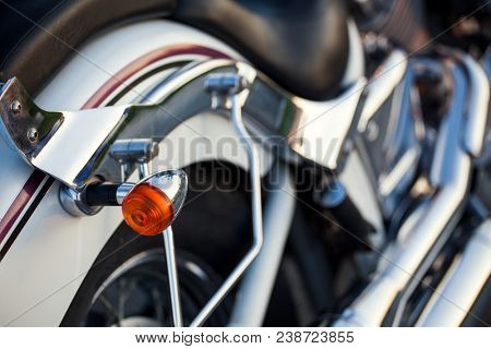Close up view of a shiny chrome motorcycle design engine with blinker.