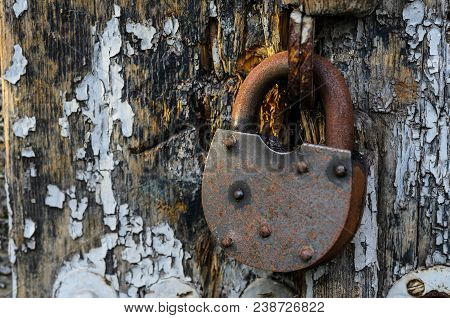 Rusty old lock on the wooden doors. Lock on the door of an old farmhouse. Village style. Close-up.  Wooden texture. Natural wood background.