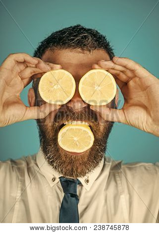 Dieting And Fitness. Vitamin Citrus At Hipster On Blue Background. Man With Long Beard Eat Lemon. Ve