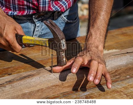 Man Feeling His Sore Hand After Having Hurt Himself While Hammering. Profession, Carpentry, Woodwork