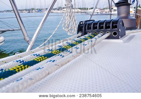 Sailboat Detailed Parts. Close Up On Winch And Rope Of Yacht Over Blue Sea. Yachting Concept. Shallo