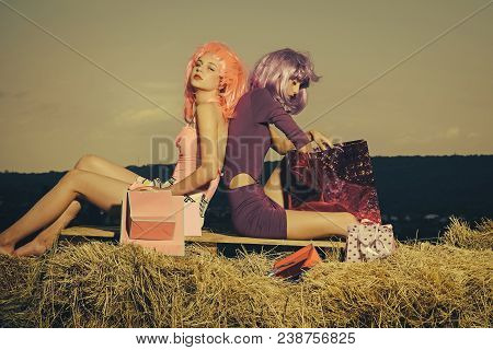 Women In Wig With Makeup On Blue Sky. Girls With Artificial Hair With Colorful Shopping Bag. Shoppin