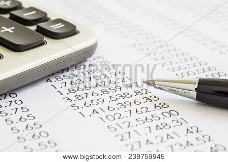 Closeup Of Financial Statements, Annual Reports With Modern Pen And Calculator In Flame, Black And W