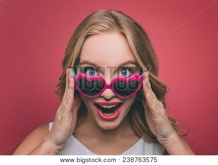 Pretty Woman With Blonde Hair Weard Sunglasses With Pink Edge. She Is Looking On Camera And Holding