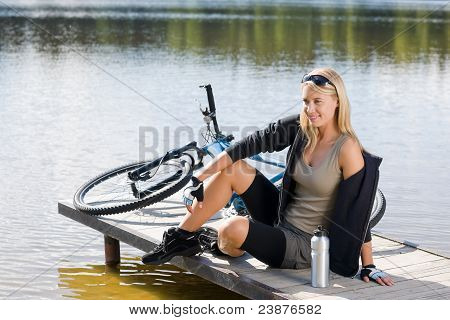 Sport Biking Young Woman Sitting By Lake