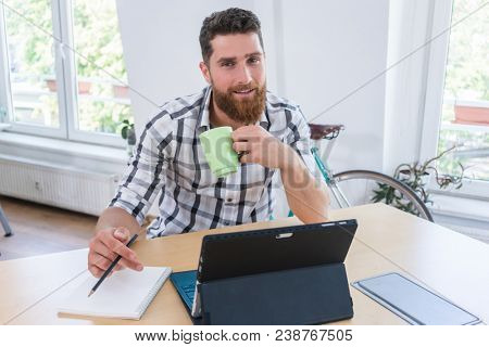 Portrait of a confident self-employed young man smiling and looking at camera, while sitting at desk in front of a tablet and a blank notebook in a modern shared office space