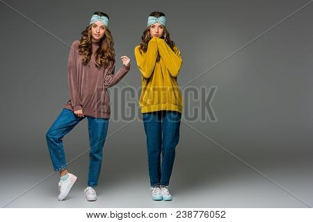 Attractive Young Twins In Sweaters Looking At Camera On Grey
