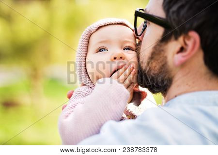 An Unrecognizable Father With His Toddler Daughter Outside In Green Sunny Spring Nature., Kissing.