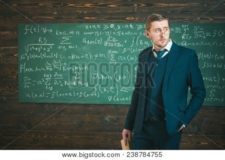 Young aristocrat in glasses holding book and posing in classroom. Elite education concept. poster