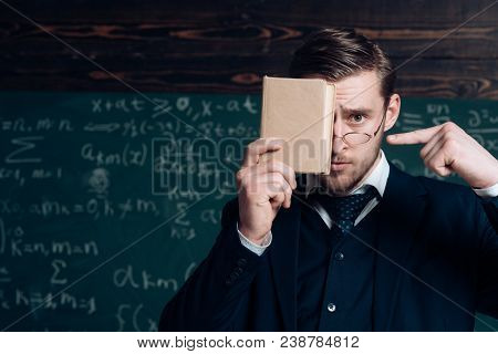Handsome Student In Suit Covering His Face With Book While Pointing At It With Other Hand. Closeup P