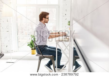 Occupational. Determined Bearded Man Sitting At The Table And Working On His Laptop