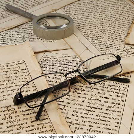 Glasses and lens on old book pages
