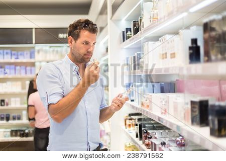 Elegant Man Choosing Perfume In Retail Store. Casual Man Testing And Buying Gift For His Lady In A B