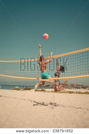 Couple Have Fun Playing Volleyball. Young Sporty Active Couple Beat Off Volley Ball, Play Game On Su