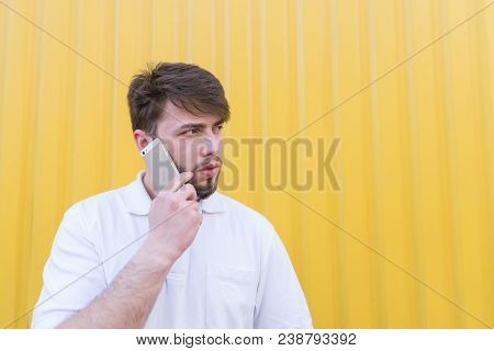 A Serious Man Speaks By Telephone On The Background Of A Yellow Wall And Looks Aside. Serious Conver