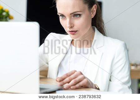 Selective Focus Of Focused Businesswoman Working On Laptop At Workplace In Office