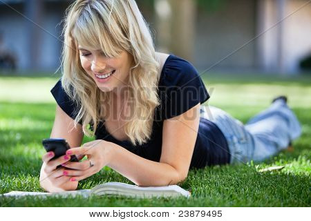 Smiling young college girl texting on a cell phone poster
