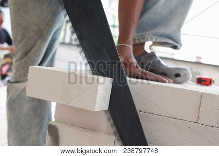 Man Worker Cutting Bricks With Crosscut Saw.