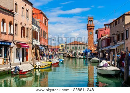 MURANO, ITALY - APRIL 20, 2016: People walking narrow canal with boats among old colorful houses of Murano - famous island in Venetian Lagoon, popular tourist destination.