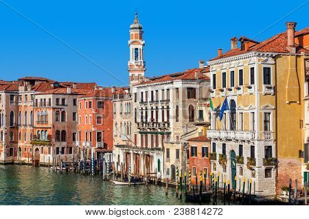 View of colorful buildings along Grand canal under blue sky in Venice, Italy.