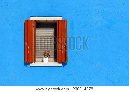 Window with wooden shutters on blue wall in Burano, Italy.