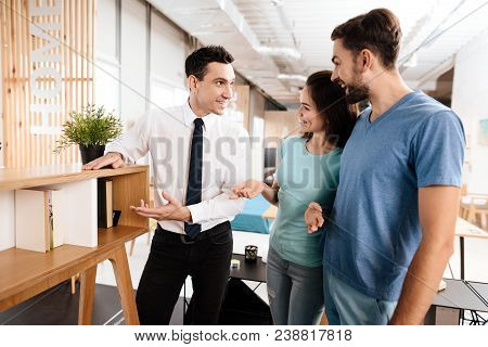 The Furniture Store Manager Demonstrates Furniture To The Buyers. A Guy And A Girl Are Listening Wit